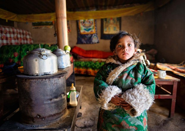 Tibetan kid wearing traditional clothes. Remote Tibetan plateau