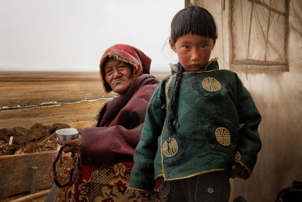 Tibetan grandmother and grandaughter in their nomad tent. Tibetan plateau