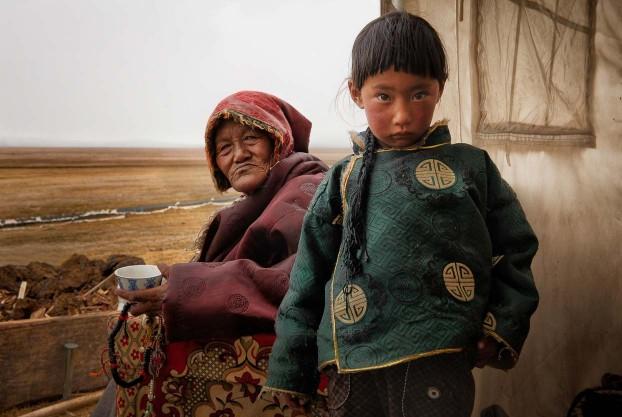 Tibetan grandmother and grandaughter in their nomad tent. Tibetan plateau